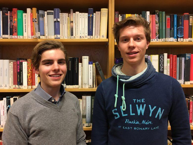 Konstantin Klingler und Moritz Stephan vor einem vollgefüllten Bücherregal.
